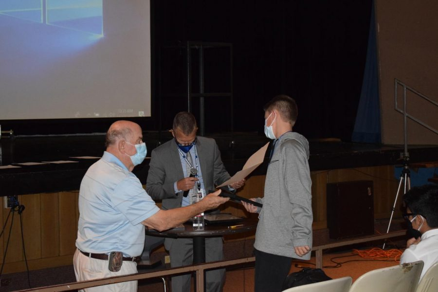 A student receives his certificate at the Judith Sapp Scholars Ceremony on Tuesday, November 17.